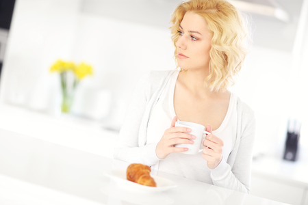 A picture of a young happy woman drinking coffee in the kitchen photo
