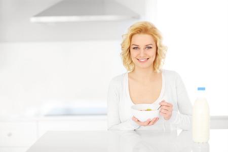 comiendo cereal: Una foto de una mujer joven comer cereales en la cocina