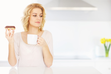 A picture of a young woman eating donut with morning coffee photo