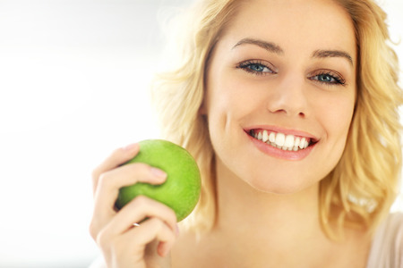 woman eating fruit: A picture of a young woman eating an apple at home Stock Photo