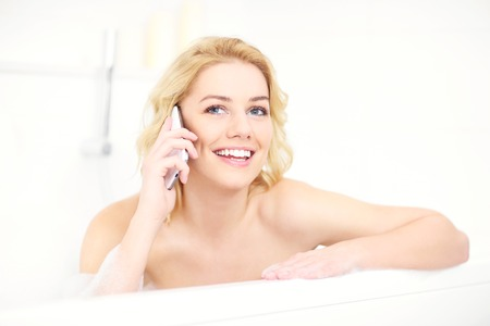 lying in bathtub: A picture of a happy woman talking on phone when taking a bath