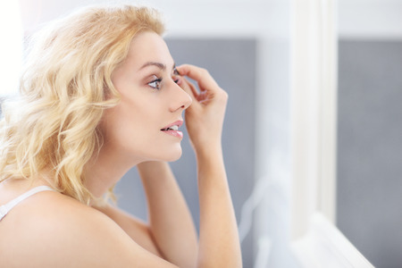 tweezing eyebrow: A picture of a young woman shaping eyebrows with tweezers in the bathroom Stock Photo