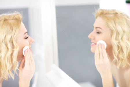 removing make up: A picture of a woman cleaning face in the bathroom
