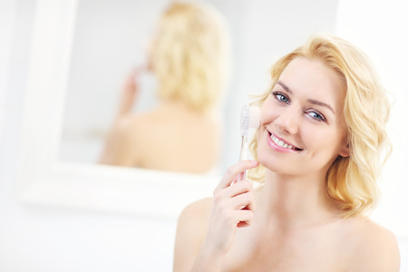 brush in: A picture of a young woman using face cleansing brush in the bathroom