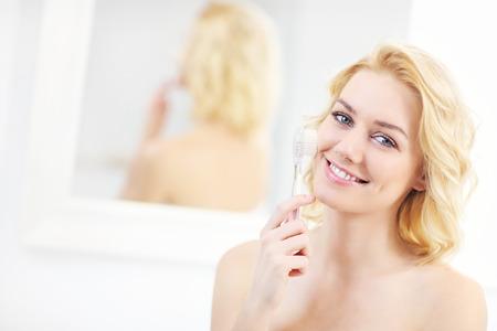 pulizia viso: Un ritratto di una giovane donna con pennello pulizia del viso in bagno Archivio Fotografico