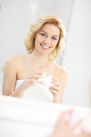 woman face cream: A picture of a young woman applying cream in the bathroom