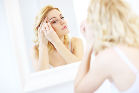 shaping: A picture of a young woman shaping eyebrows with tweezers in the bathroom Stock Photo