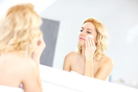 remover: A picture of a woman cleaning face in the bathroom