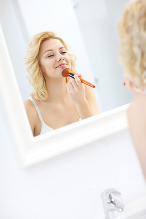 face powder: A picture of a young woman applying face powder in the bathroom