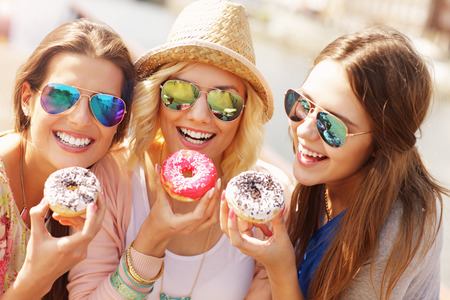 donut: Group of friends eating donuts in the city