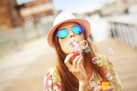 A picture of a happy woman blowing soap bubbles in the city Stockfoto