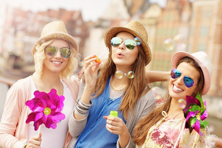 a picture of group of friends blowing soap bubbles in the city Фото со стока - 40390422