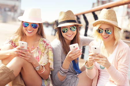 A picture of group of friends using smartphones in the city Stockfoto