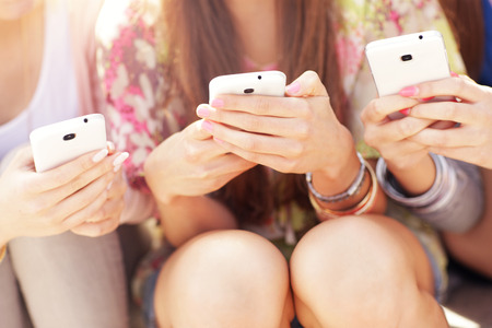 chat group: A picture of group of friends using smartphones in the city Stock Photo