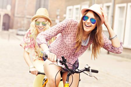 Een foto van twee meisje vrienden rijden op een tandem fiets in de stad Stockfoto