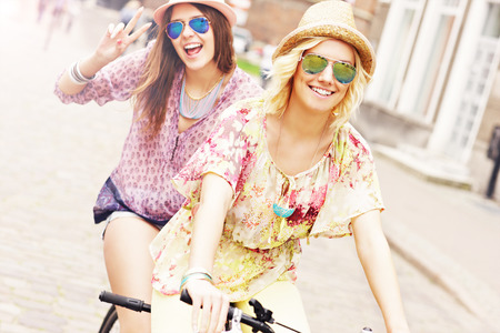 tandem bicycle: A picture of two girl friends riding a tandem bicycle in the city