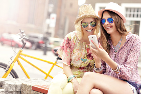 tandem bicycle: A picture of two girl friends using smartphone while riding tandem bicycle Stock Photo