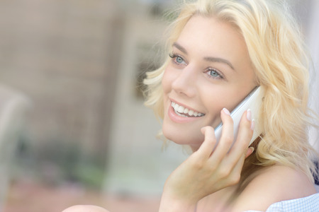 woman on phone: A picture of a young pretty woman sitting in the window and talking on the phone