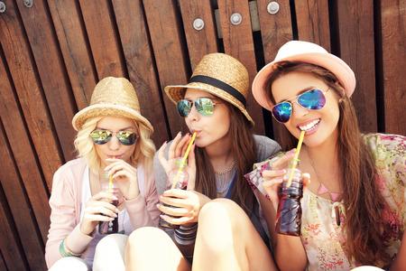 桟橋にソーダを飲んで女の子の友人のグループの写真