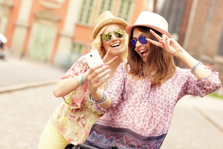 A picture of two girl friends using smartphone while riding tandem bicycle photo