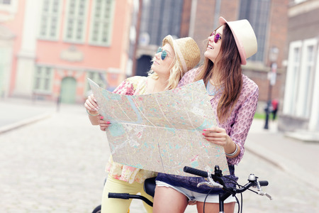 lost city: A picture of two girl friends using a map and riding a tandem bicycle in the city Stock Photo