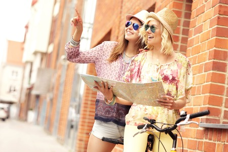 A picture of two girl friends using a map and riding a tandem bicycle in the city Stock Photo