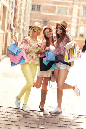 A picture of a group of joyful girl friends shopping in the city
