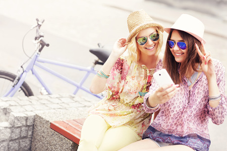 tandem bicycle: A picture of two girl friends riding a tandem bicycle and taking selfie in the city Stock Photo