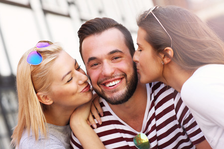women kissing women: A picture of two attractive women kissing a man in the city