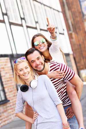 young adults: A picture of a group of happy friends smiling to the camera and pointing at copy space Stock Photo