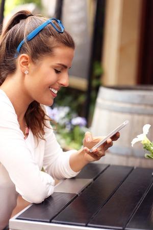mujeres felices: Una imagen de una mujer feliz que usa smartphone en el caf� Foto de archivo