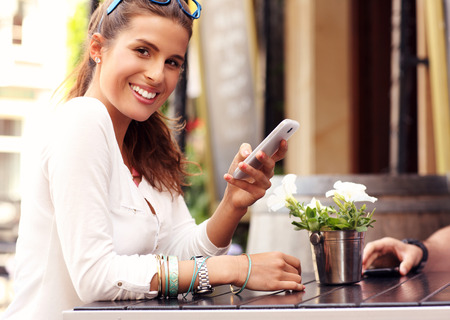woman bar: A picture of a happy woman using smartphone in cafe Stock Photo