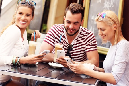 friends drinking: A picture of a group of friends resting in an outdoor cafe and using smartphones