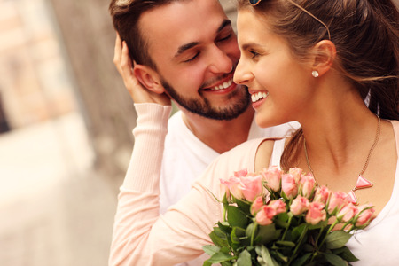 Een foto van een jong romantisch koppel met bloemen in de stad Stockfoto