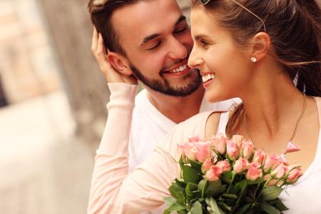 mujer con rosas: Una foto de una joven pareja romántica con flores en la ciudad