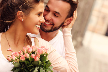 romantic couple: A picture of a young romantic couple with flowers in the city Stock Photo