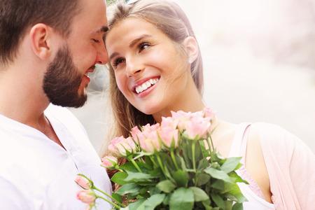 Een beeld van een jonge romantisch paar met bloemen in de stad