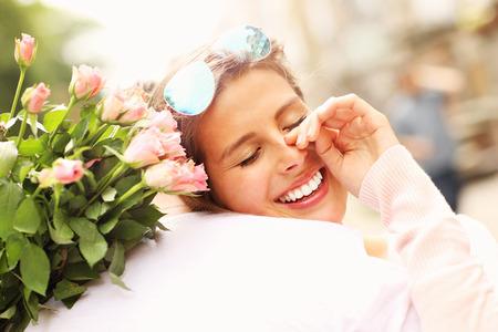 fille pleure: Une image d'une jolie femme tenant des fleurs et étreignant un homme Banque d'images