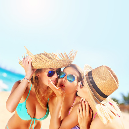 3 women kissing a friend on the beach party Stockfoto