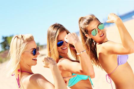 uygunluk: Sahilde kaslarını gösteren seksi bir grup kadının bir resmi