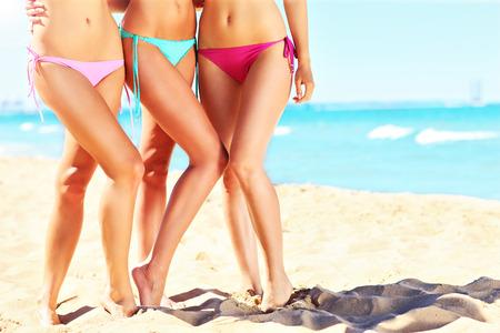 ビーチでビキニの女性の脚