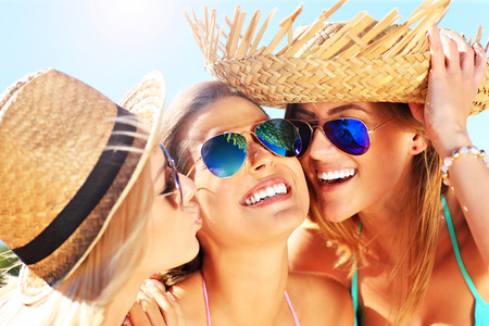 3 women kissing a friend on the beach party Stock Photo