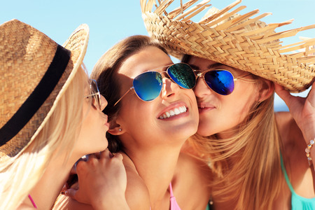 party friends: A picture of two women kissing a friend on the beach party Stock Photo