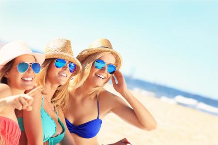 해변에서 일광욕을하는 친구들의 그룹 사진