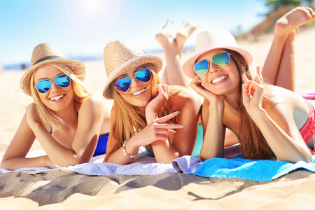A picture of a group of friends sunbathing on the beach Standard-Bild