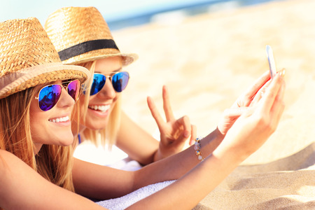 해변에서 셀카를 타는 친구들의 사진 스톡 콘텐츠