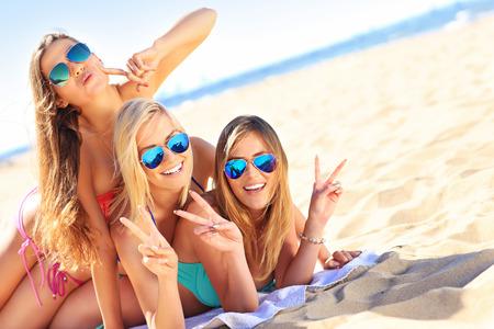 ビーチでの楽しみを持っている女性のグループの写真