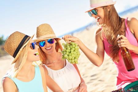 comiendo frutas: Una foto de un grupo de amigos que tienen comida campestre en la playa