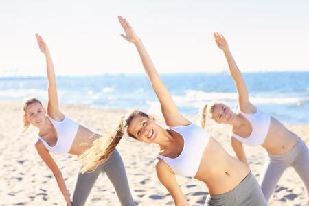 mujeres juntas: Una foto de un grupo de mujeres practicando yoga en la playa Foto de archivo