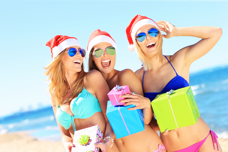 people together: A picture of a group of women in bikini and Santas hats holding presents on the beach